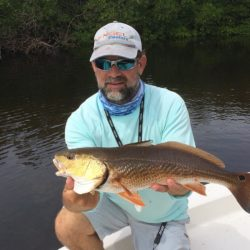 a fisherman with a naples redfish