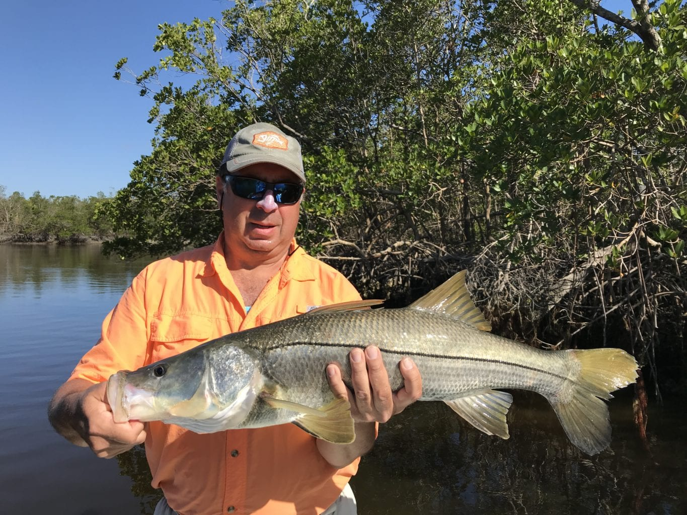 a fisherman with a snook caught in naples